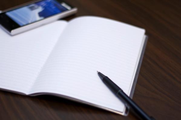 スマホとノートとペンの画像