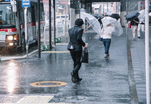 大雨と強風の中、出社する社畜ビジネスマンの画像